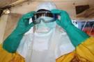 Un médecin revêt un équipement de protection avant de rencontrer un patient infecté par Ebola.