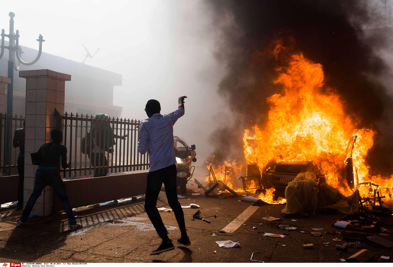 Une voiture brûle devant le Parlement à Ouagadougou, le 30 octobre 2014.