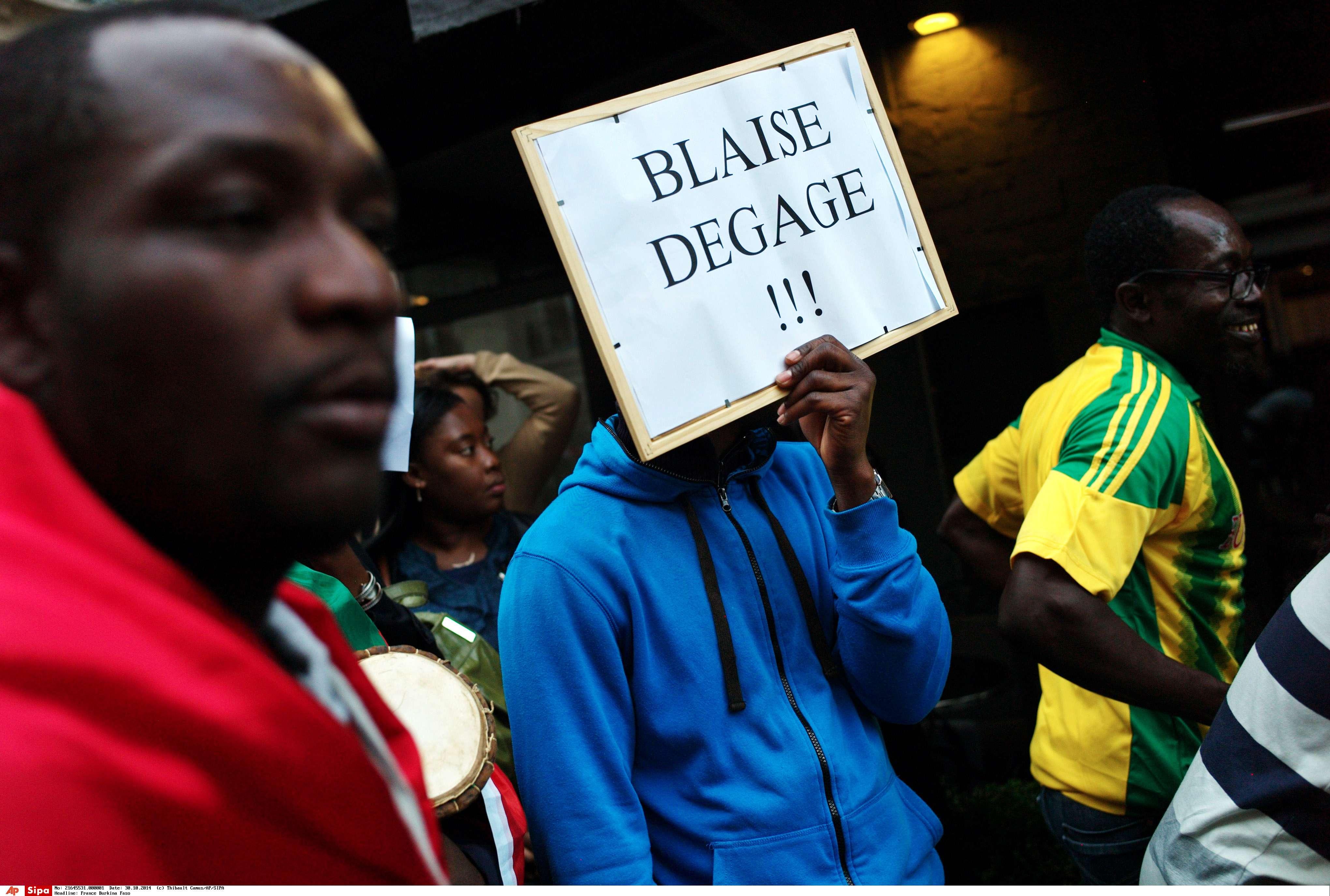"""Un homme tient une pancarte """"Blaise dégage"""" pour demander la chute de Blaise Compaoré, le 30 octobre 2014."""