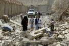 Des Yéménites marchent dans les décombres d'immeubles du quartier Al-Nahda dans la capitale, Sanaa, après des frappes aériennes menées par l'Arabie Saoudite
