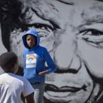 Des enfants sud-africains jouent devant une fresque murale représentant Nelson Mandela, le 2 mai 2014, dans le quartier Soweto de Johannesburg