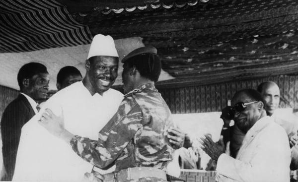 """L'accolade entre Moussa Traoré (g) et Thomas Sankara (d) met fin à la """"guerre des pauvres"""" entre le Mali et le Burkina, le 17 janvier 1986 à Yamoussoukro, en Côte d'Ivoire."""