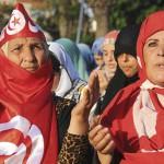 Des Tunisiennes voilées du drapeau national prient devant la mosquée Zitouna, à Tunis, le 8 août 2013.