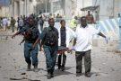 Des gardes des bureaux des Nations unies et des soldats somaliens portent le corps d'un de leurs collègues après une attaque à Mogadiscio, le  26 juillet 2016.
