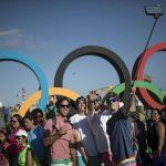 Des passants posent devant les anneaux olympique à la plage de Copacabana à Rio, le 31 juillet 2016.