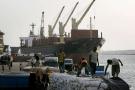 Des hommes déchargent un bateau dans le port de Conakry, en mars 2008.