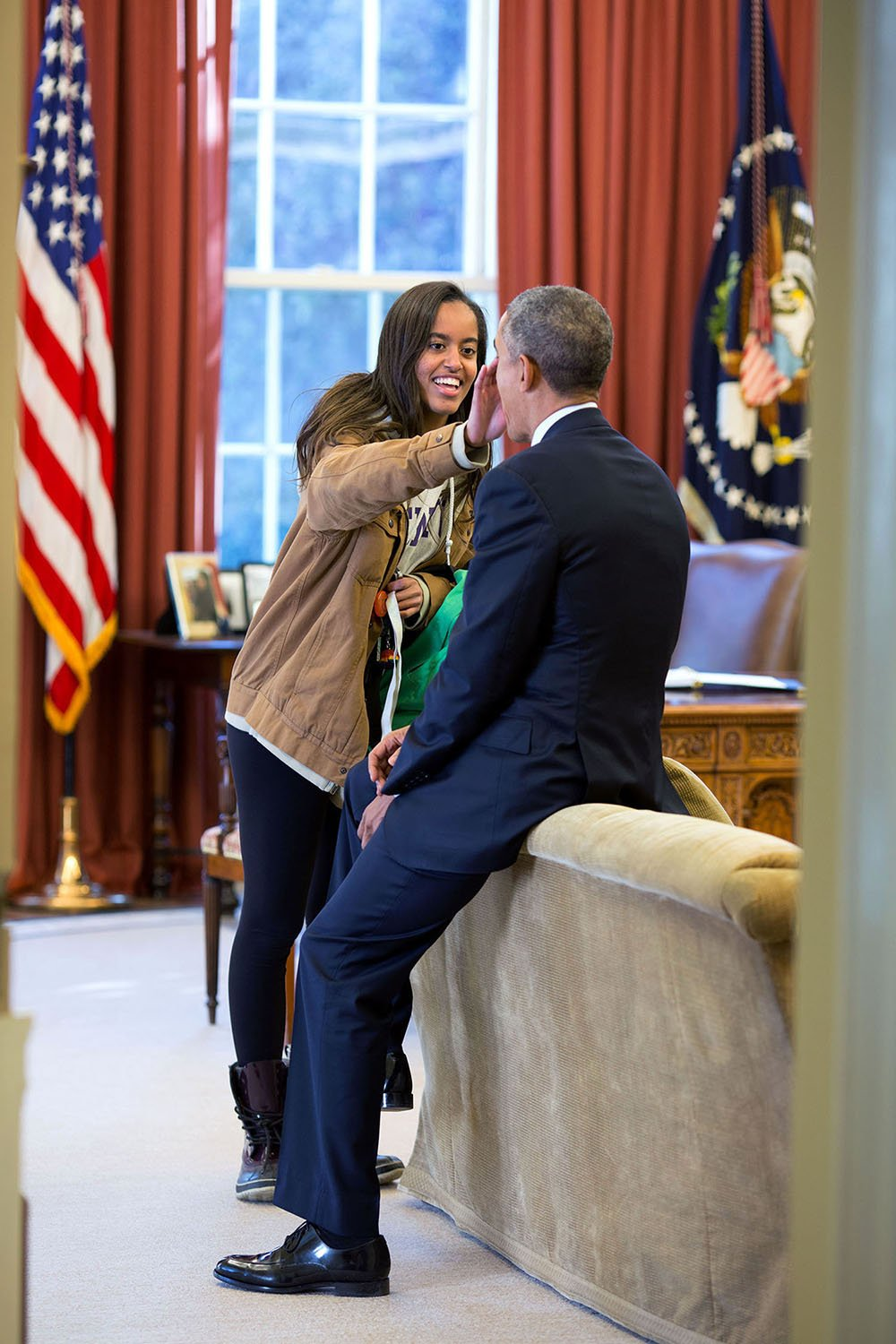 "Feb. 23, 2015 ""The President's daughter Malia stopped by the Oval Office one afternoon to see her dad and, while they were talking, she wiped something from his face."" (Official White House Photo by Pete Souza) This official White House photograph is being made available only for publication by news organizations and/or for personal use printing by the subject(s) of the photograph. The photograph may not be manipulated in any way and may not be used in commercial or political materials, advertisements, emails, products, promotions that in any way suggests approval or endorsement of the President, the First Family, or the White House."