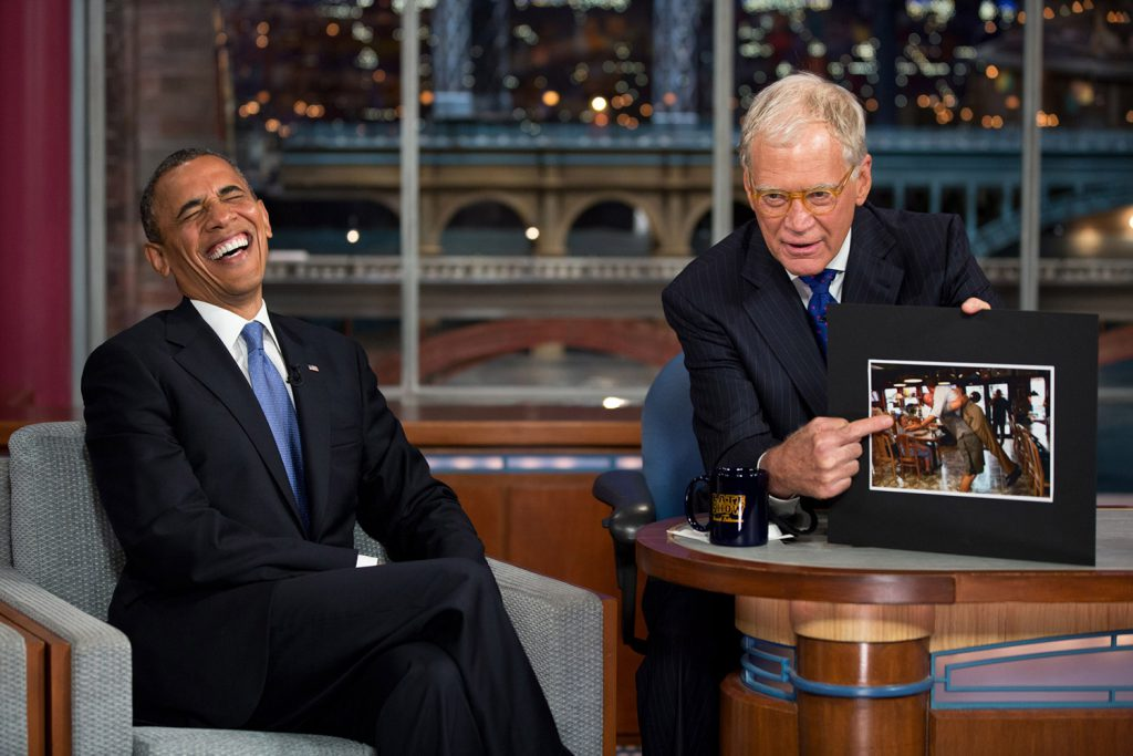 "President Barack Obama reacts to a photograph during an interview with David Letterman during a taping of the ""Late Show with David Letterman"" at the Ed Sullivan Theater in New York, on September 18, 2012"