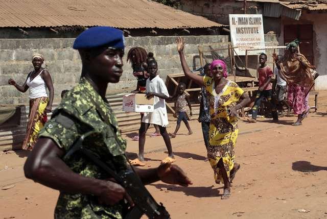 Des Gambiens célèbrent la victoire de la coalition formée contre le président  Yahya Jammeh alors qu'un soldat monte la garde, à Serrekunda le 2 décembre 2016.