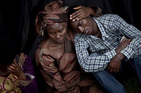 Deux personnes attendent le début de la cérémonie publique du 20ème anniversaire du génocide au Rwanda, à Kigali, le 4 avril 2014.