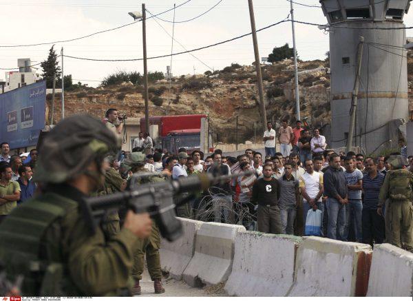 A Hébron, les soldats israéliens arme au poing pendant que les palestiniens attendent pour traverser l'un des dix-huit check-points.