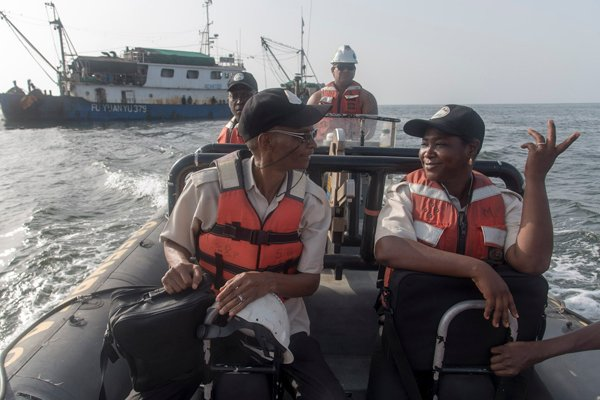 Des inspecteurs guinéens de la pêche devant un bateau chinois arrêté pour pêche illégale.