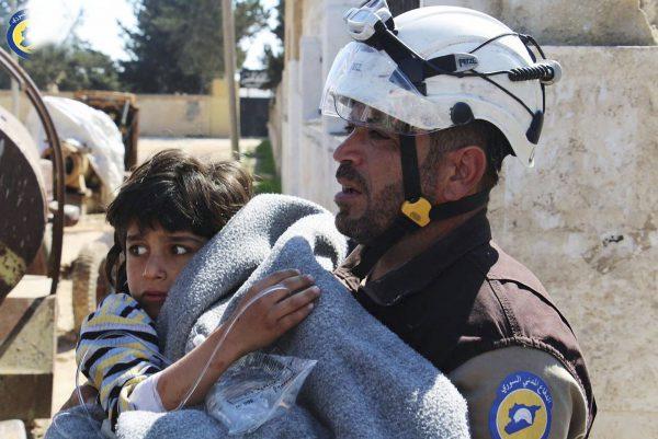 Un volontaire de la Défense civile syrienne secourant un enfant blessé, à Khan Cheikhoun, dans le nord-est du pays, le 4avril 2017.