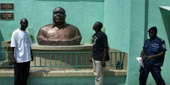 Des Congolais posent devant le buste de Laurent-Désiré Kabila, le 17 mai 2005, à Kinshasa.