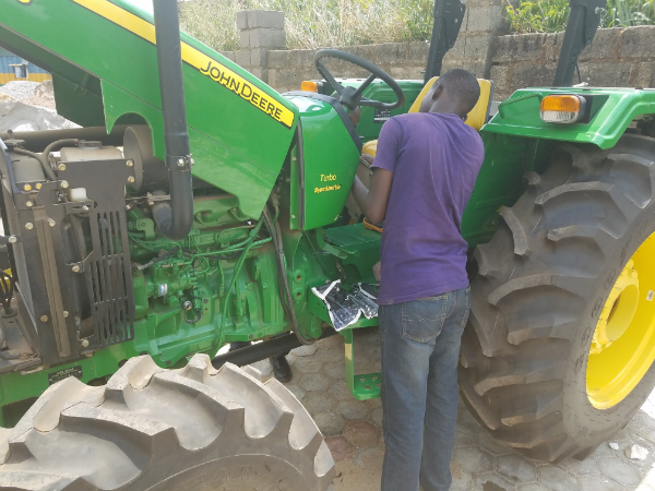 Un ingénieur de Hello Tractor en pleine réparation d'un tracteur.