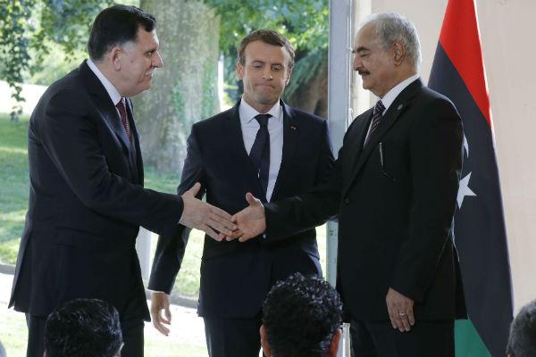 Le président du conseil présidentiel libyen Fayez al-Sarraj (g.) et le commandant de l'armée nationale libyenne Khalifa Haftar, se serrent la main sous le regard d'Emmanuel Macron, président français, à l'issue de la rencontre de ce mardi 25 juillet près de Paris.