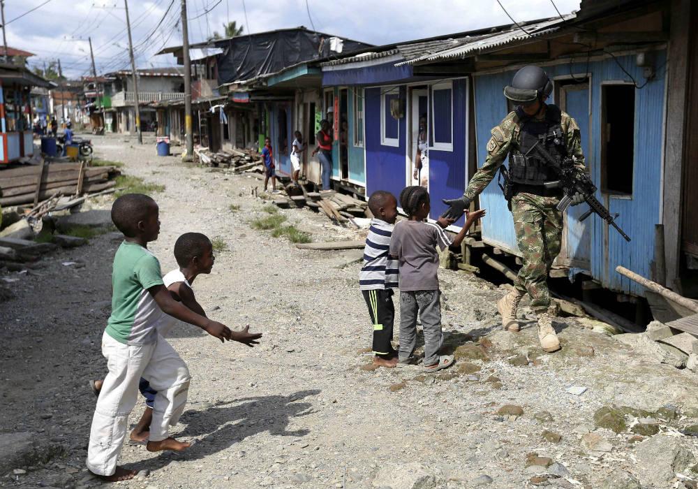 Des enfants saluent un soldat des Forces spéciales de la Marine colombienne, venues en renfort pour lutter contre la violence des gangs se disputant le contrôle de Buenaventura, le 27 mars 2014.