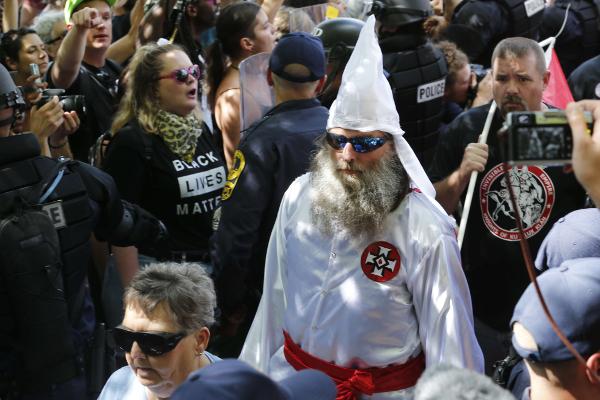 Un homme revêtant la tenue du  Ku Klux Klan, à Charlottesville, aux États-Unis, le 8 juillet. Il défile devant des militants anti-racistes.