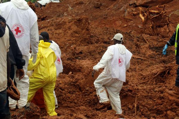 Des volontaires de la Croix Rouge en Sierra Leone recherchent des corps après une coulée de boue à Freetown, lundi 14 août 2017.
