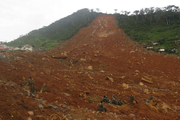 Des membres des forces de sécurité sierra-léonaises se reposent après avoir cherché des corps sous une coulée de boue à la périphérie de la capitale Freetown, mardi 15 août 2017.