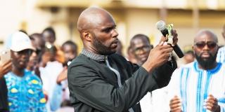 Kemi Seba brûlant un billet de 5 000 FCFA lors d'un rassemblement, le 19 août 2017 à Dakar.