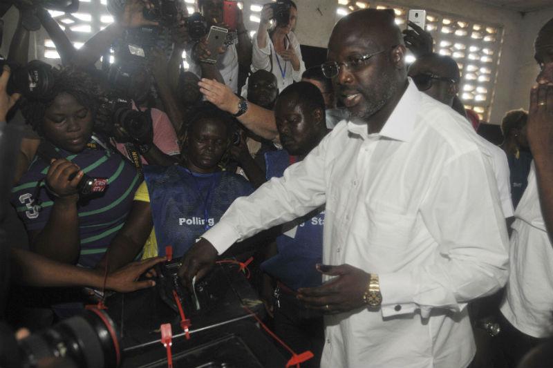 George Weah glisse son bulletin dans l'urne à Monrovia le 10 octobre.