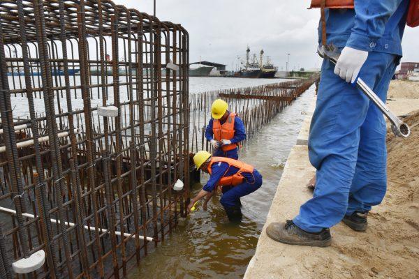 Ouvriers installant la plate-forme de réparation d'un roulier dans le port d'Abidjan, le 14septembre 2017.