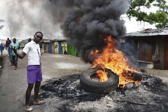 Un jeune homme prend la pose devant des pneus en train de brûler durant des manifestations à Mombasa, dans le sud du pays. AP/SIPA