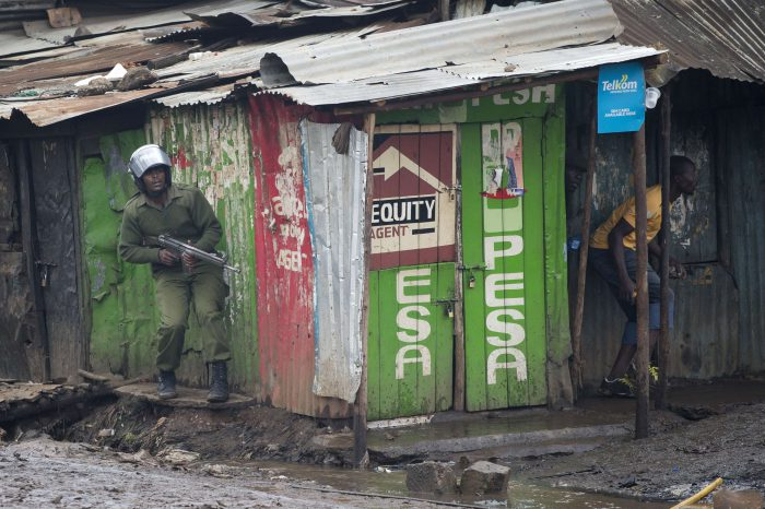 Arme à la main, un policier poursuit un manifestant durant des affrontements à Kibera, un bidonville de Nairobi.