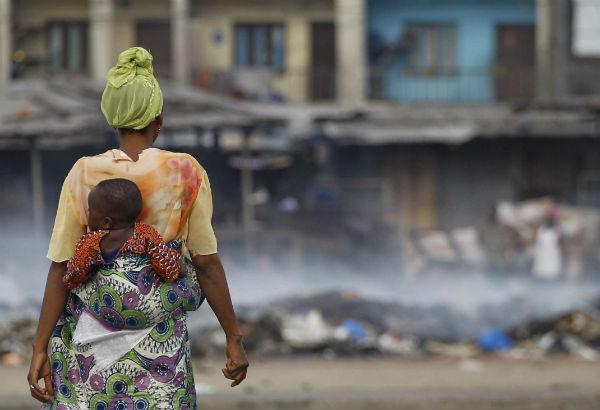 Une femme observe les décombres fumantes au marché d'Abobo, pendant la crise postélectorale, le 4 mars 2011.