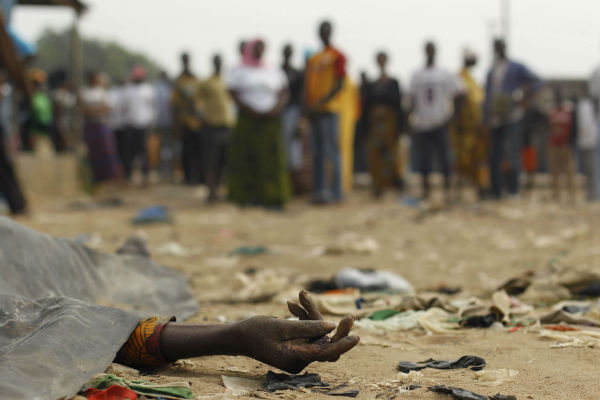 Une foule observe une victime de tirs, en janvier 2011 dans le quartier d'Abobo, à Abidjan.