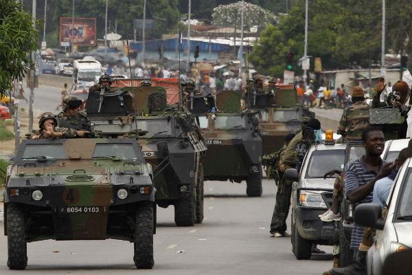 Une colonne de blindés de l'armée française croise un patrouille des Forces républicaines, en avril 2011 à Abidjan.