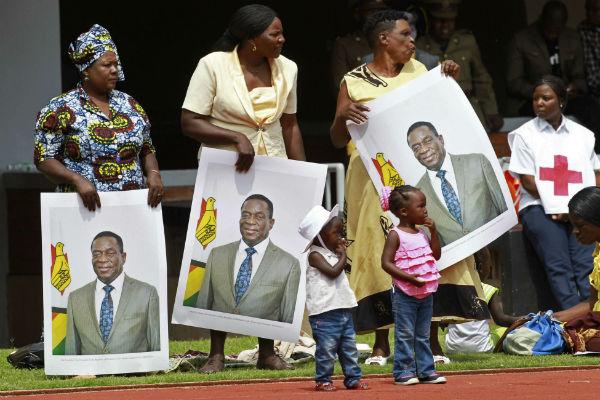 Des Zimbabwéens portent des portraits d'Emmerson Mnangagwa lors de l'investiture, ce vendredi 24 novembre 2017 à Harare.