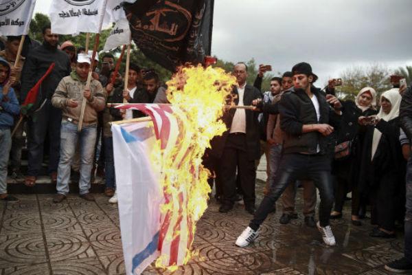 Des Palestiniens brûlent un drapeau américain et un drapeau israélien à Gaza, ce mercredi 6 décembre 2017.