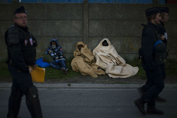 Des policiers français passent devant des migrants érythréens, lors d'une opération à Calais en octobre 2017.