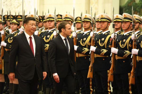 Le président de la République française Emmanuel Macron au côté de son homologue chinois Xi Jinping, alors qu'ils passent en revue la garde d'honneur lors d'une cérémonie de bienvenue au Grand Palais du Peuple, le 9 janvier 2018 à Pékin