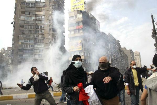 Des manifestants égyptiens fuient la police anti-émeutes qui leur tirent du gaz lacrymogène au Caire, le vendredi 28 janvier 2011