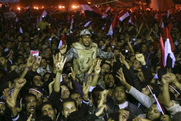 Des Égyptiens tenant un soldat sur la place Tahrir après la démission du président Hosni Moubarak et la remise du pouvoir à l'armée au Caire, le 11 février 2011