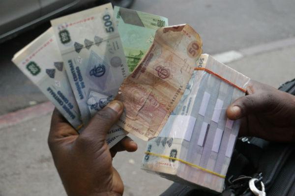 Des francs congolais dans les mains d'un cambiste clandestin, en juillet 2017 à Kinshasa.