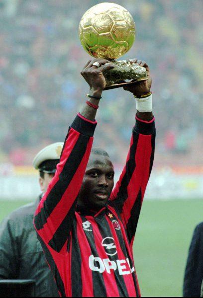 Georges Weah en 1996, alors au Milan AC, lève son ballon d or sous les applaudissement du public.