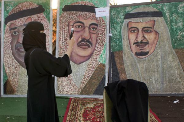 une femme prend des photos de portraits du roi d'Arabie saoudite et de son fils, prince héritier, à Jeddah, le 8 février 2017.
