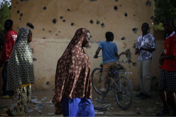 Des Maliens devant un poste de police de Gao lourdement bombardé en février 2013 par des combattants de Mujao.