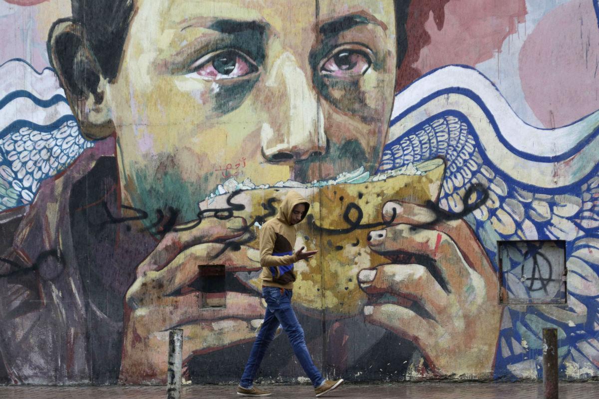 Un jeune homme passe près d'une fresque, place Tahrir, au Caire, en janvier 2016.