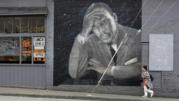 Une femme passe devant une grande peinture murale du pasteur Martin Luther King Junior sur le côté d'un restaurant, peint par l'artiste James Crespinel dans les années 1990 et restauré plus tard, le long de la route Martin Luther King Junior. À Seattle (États-Unis), le 3 avril 2018