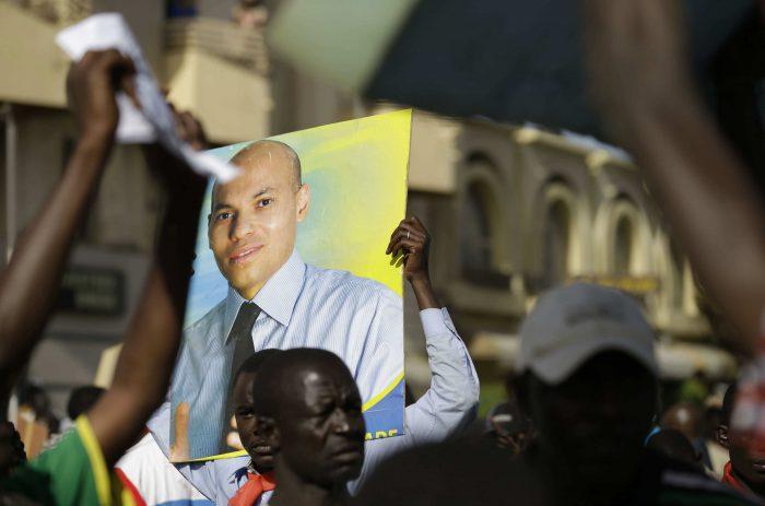 Un manifestant brandit un poster de Karim Wade, dans les rues de Dakar, en avril 2013.