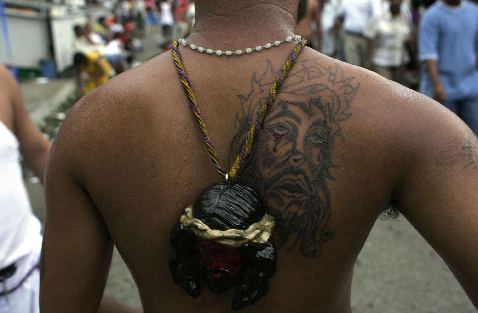 Un tatouage et un pendentif du Christ.