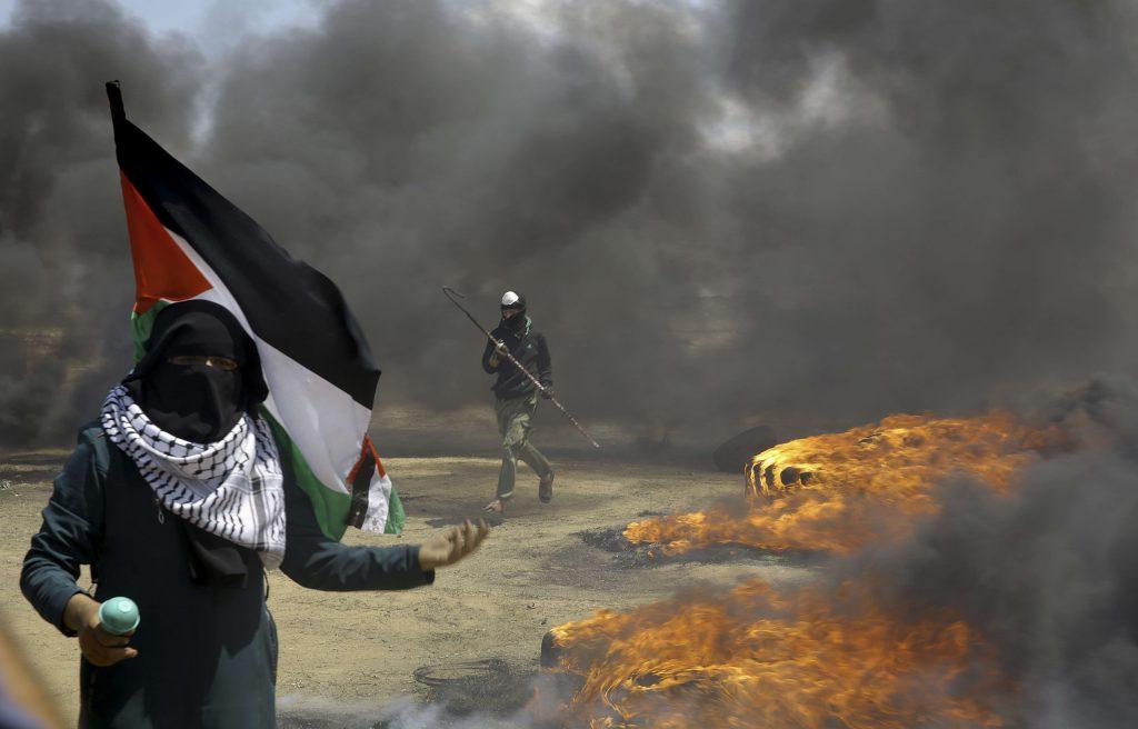 Une femme brandit un drapeau palestinien alors qu'un manifestant brûle des pneus près de la frontière israélienne, à l'est de Khan Younis, dans la bande de Gaza, lundi 14 mai 2018, avant l'inauguration de l'ambassade des Etats-Unis à Jérusalem.