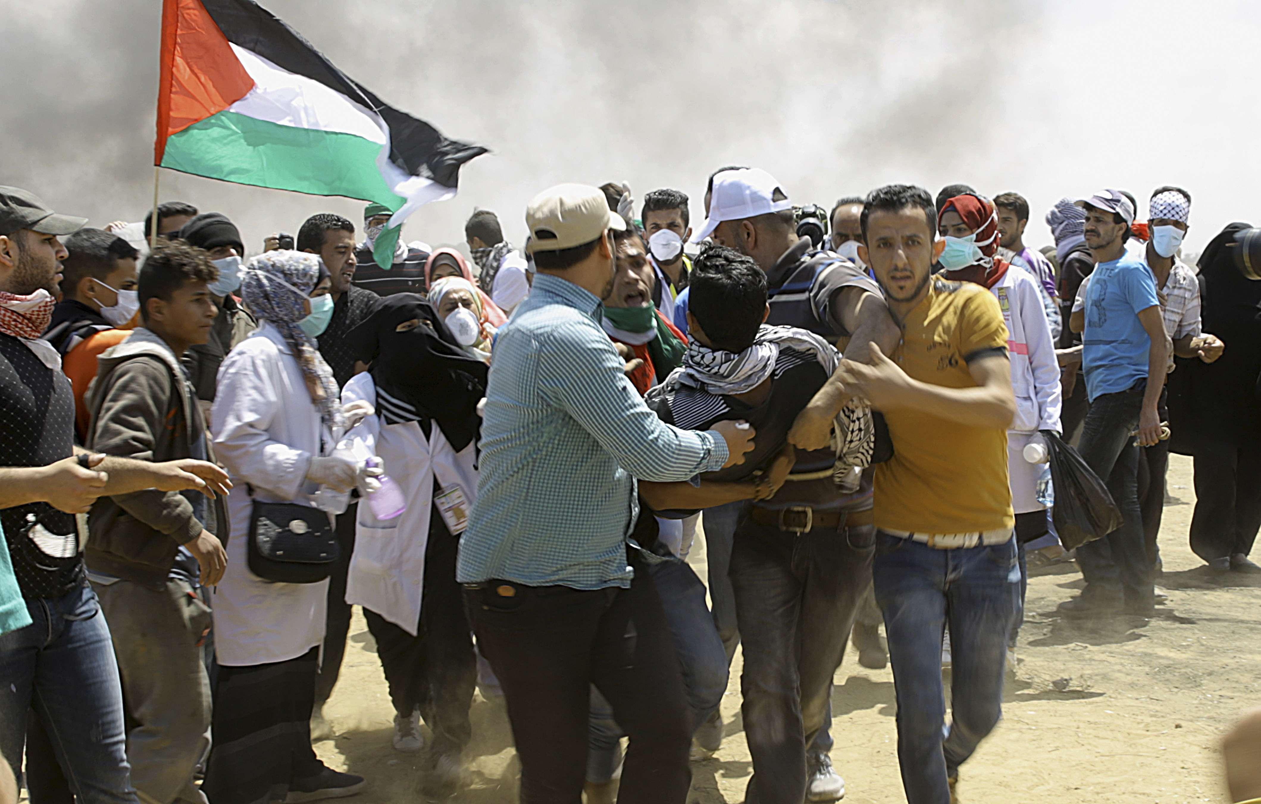 Des manifestants palestiniens évacuent un jeune blessé près de la frontière israélienne, à l'est de Khan Younis, dans la bande de Gaza, lundi 14 mai 2018, peu avant l'inauguration de l'ambassade des Etats-Unis à Jérusalem.