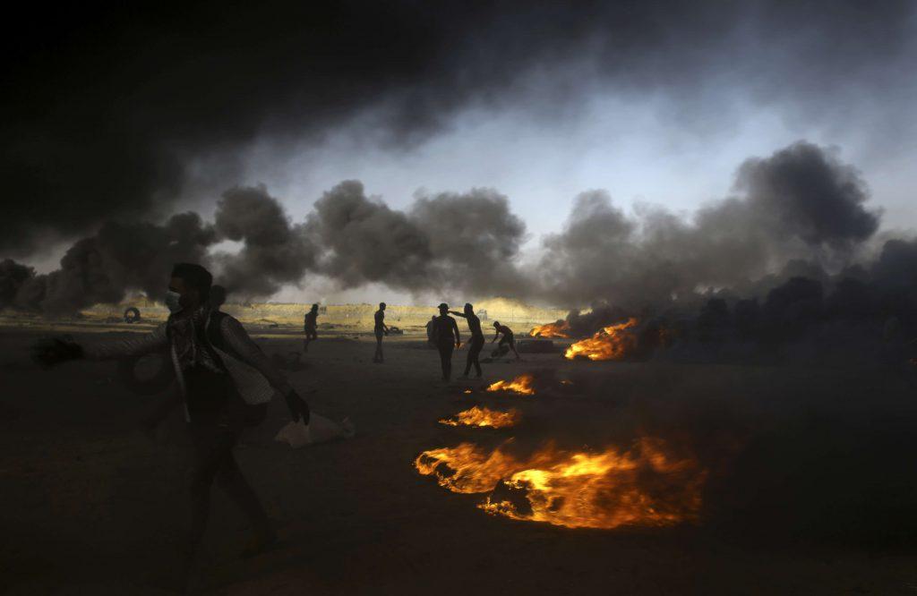 Des manifestants palestiniens brûlent des pneus lors d'une manifestation à la frontière de la bande de Gaza avec Israël, à l'est de Khan Younis, mardi 15 mai 2018.