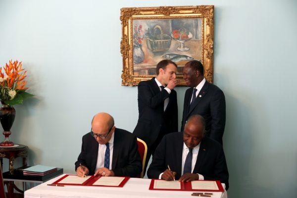Avec son homologue français, Emmanuel Macron, lors de la signature d'un accord économique, le 30novembre 2017, à Abidjan. Au premier plan, le ministre français des Affaires étrangères, Jean-Yves Le Drian, et le Premier ministre ivoirien, Amadou Gon Coulibaly